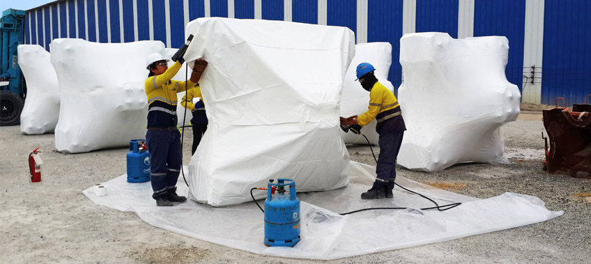 Three CEA Project Logistics Staff apply shrink wrapping to cargo