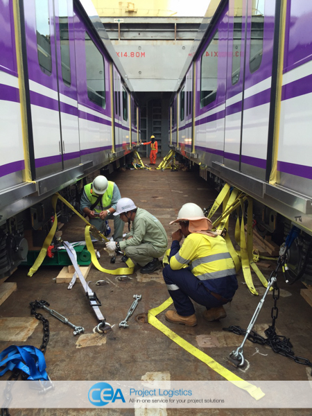 Train carriages in ships hull being inspected