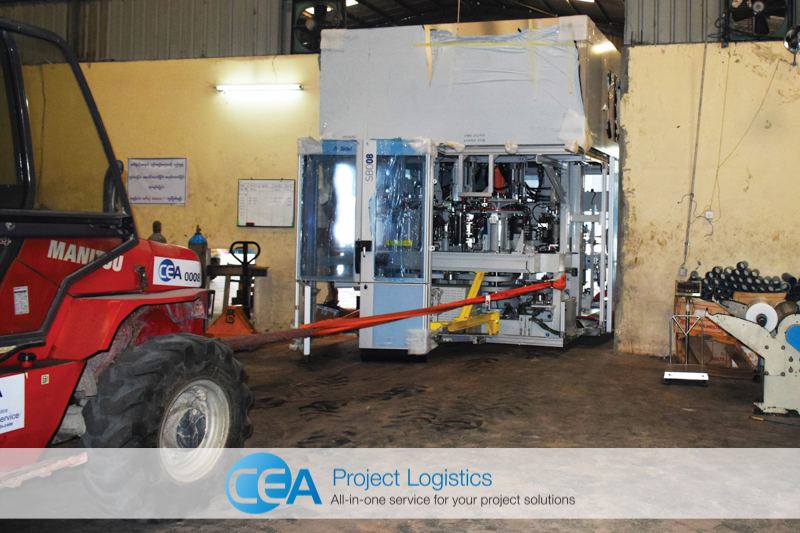 Bottle blower pulled through hole in the wall by forklift - CEA Project Logistics Myanmar