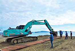 excavator laying steel plates on the beach