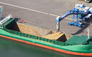 Vessel in port receiving grain from a grani feeder into its hull - Agro Logistics