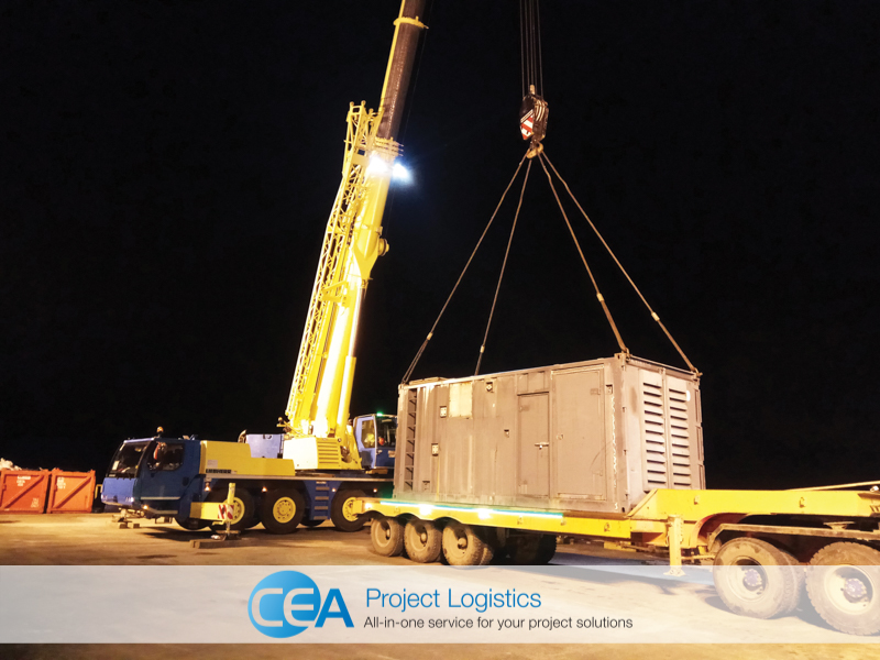 Crane loading generator on to flatbed trailer for transportation