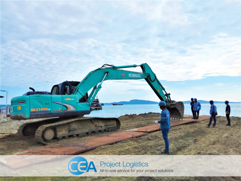 excavator installing steel plates on the beach