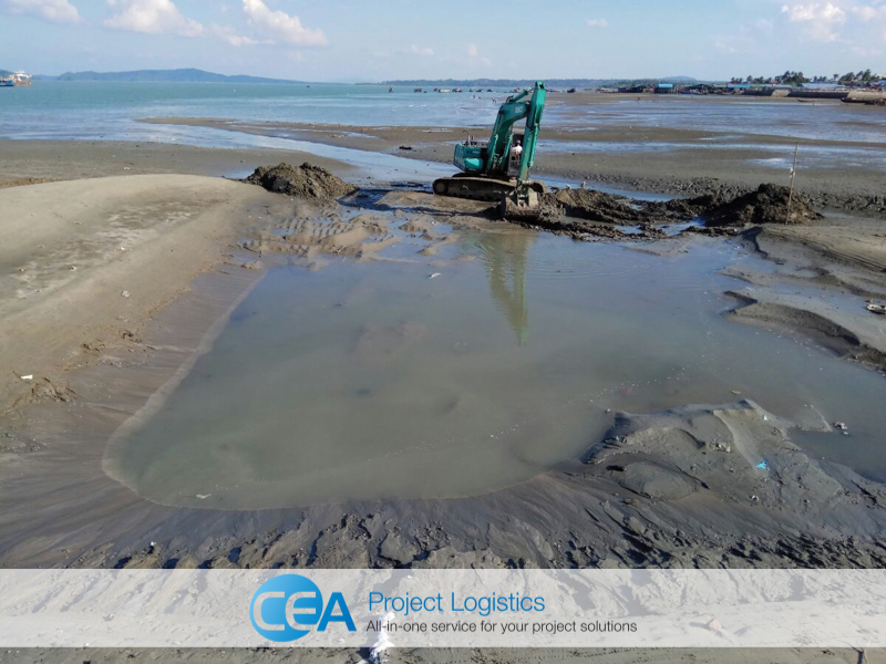 Excavator clearing beach landing area